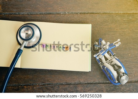 conceptual image with INSURANCE word block on note pad with light effect.handcrafted souvenir and stethoscope on wooden background