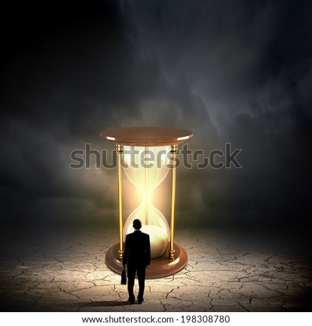 Conceptual image with sandglass and rear view of businessman