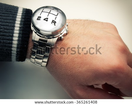 Conceptual image with speed gear stick marks and wrist watch.