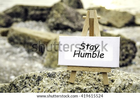conceptual image with word STAY HUMBLE on white canvas and wooden easel.Blurred rock and beach background at sunset. - stock photo