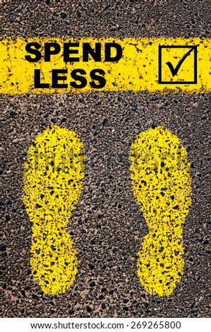 Conceptual image with yellow paint footsteps on the road in front of horizontal line over asphalt stone background. Message Spend Less and check mark sign - stock photo