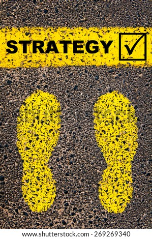 Conceptual image with yellow paint footsteps on the road in front of horizontal line over asphalt stone background. Word Strategy and check mark sign - stock photo