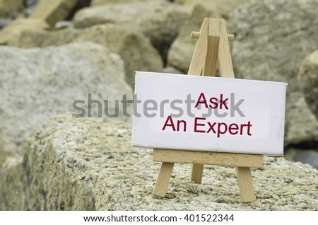 conceptual image,  word ASK AN EXPERT on white canvas frame and wooden tripod stand.blur rock textures background - stock photo