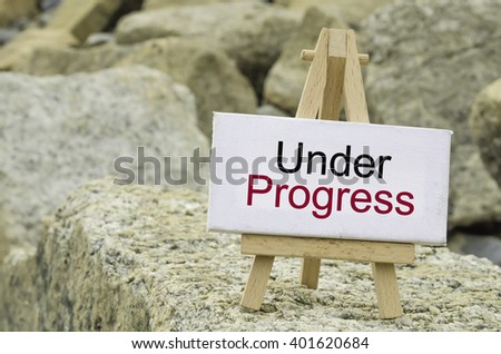 conceptual image,  word UNDER PROGRESS on white canvas frame and wooden tripod stand.blur rock textures background - stock photo