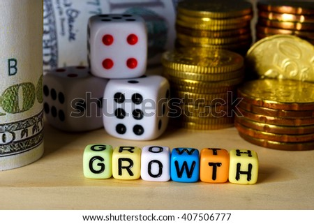 Conceptual images of hundred dollar bills, dices and golden coins with word GROWTH on wooden table.