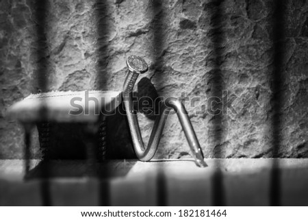 Conceptual jail photo with iron nail sitting behind out of focus bars artistic conversion