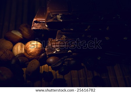 conceptual lit chocolate, nuts and grains of coffee - stock photo