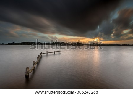 Conceptual Mood Concept Dark lake landscape during sunset on a rainy stormy day - stock photo