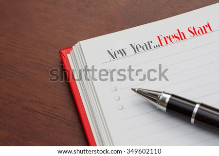 Conceptual,notebook on a wooden table. open diary and pen with new year,fresh start words - stock photo