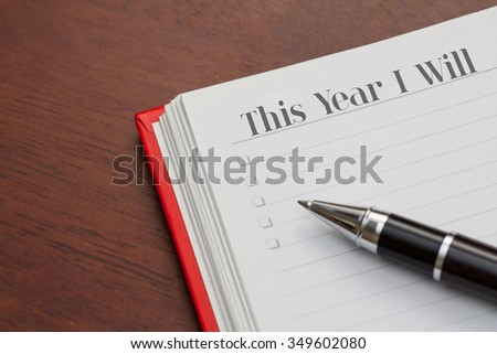 Conceptual,notebook on a wooden table. open diary and pen with this year i will words - stock photo