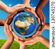 Conceptual peace and cultural diversity symbol of multiracial hands making a circle together around the world the Earth globe on blue sky and green grass background. - stock