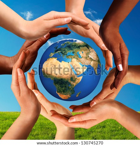 Conceptual peace and cultural diversity symbol of multiracial hands making a circle together around the world the Earth globe on blue sky and green grass background. - stock photo