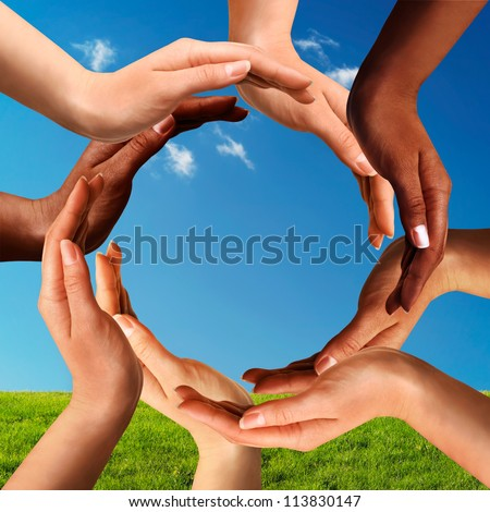 Conceptual peace and cultural diversity symbol of multiracial hands making a circle together on blue sky and green grass background.