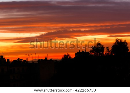Conceptual photo of city downtown at sunrise/sunset with skyline silhouette against a beautiful orange sky - stock photo