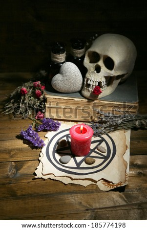 Conceptual photo of love magic. Composition with skull, dried herbs and candle on  dark wooden background