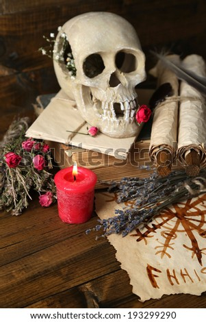 Conceptual photo of love magic. Composition with skull, voodoo doll, dried herbs and candle on  dark wooden background - stock photo