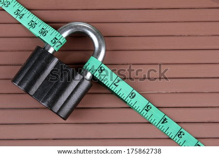 Conceptual photo of unlocking  secret of weight loss. On color wooden background - stock photo