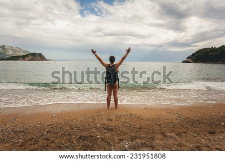 Conceptual photo of young man wearing backpack stretching out hands on sea beach - stock photo