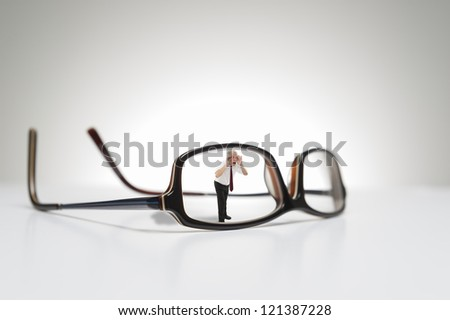 Conceptual photograph of life size glasses and a male model looking through one side of the eyeglasses. - stock photo