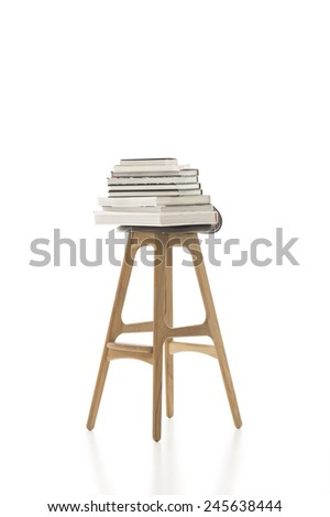 Conceptual Piled Books on Top of Tall Single Chair, with Wooden Legs, Isolated on White Background. Emphasizing Copy Space. - stock photo