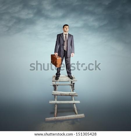 Conceptual portrait of a businessman on the bridge - stock photo