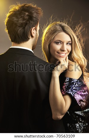 Conceptual portrait of a young couple in elegant evening dresses