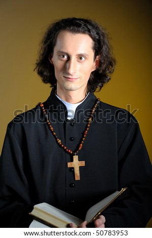 conceptual portrait of Praying priest with wooden cross. yellow background - stock photo