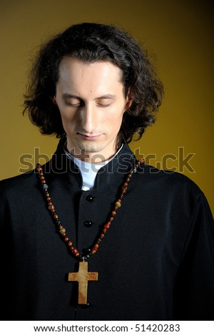 conceptual portrait of Praying priest with wooden cross . yellow background - stock photo
