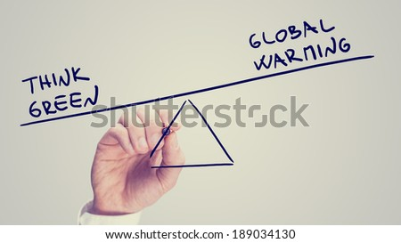 Conceptual retro image of whether to choose ecological awareness over comfort with a man drawing a diagram of a seesaw on a virtual screen with phrase Think green weighted heavily than Global warming.