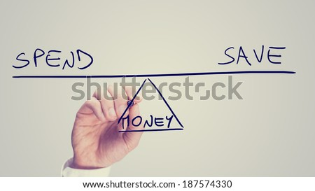 Conceptual retro image of whether to Spend or Save your Money with a man drawing a diagram of a seesaw on a virtual screen balancing the two concepts of - Spend - Save - in equilibrium. - stock photo