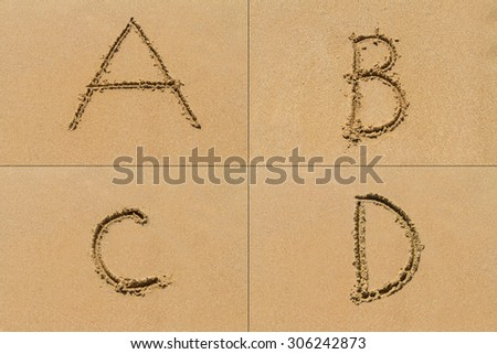Conceptual set of A B C D letter of the alphabet written on sand with upper case.