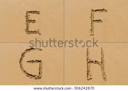 Conceptual set of E F G H letter of the alphabet written on sand with upper case.