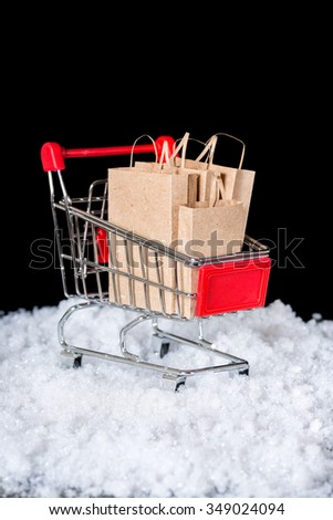 Conceptual shopping cart with paper bags in snow is isolated on black background, closeup - stock photo