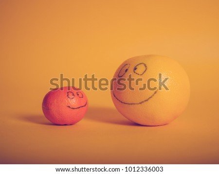 Conceptual shot of a clementine and a grapefruit with smiles painted on them