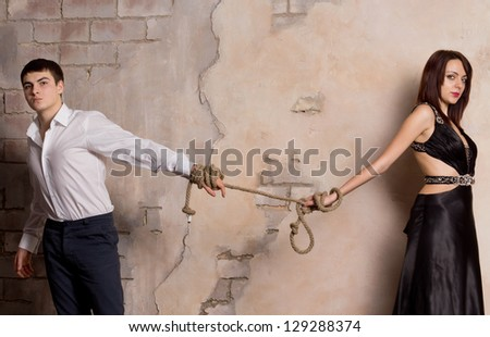 Conceptual shot of man and woman pulling a rope - stock photo