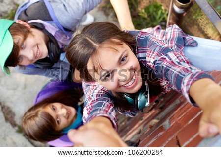 Conceptual shot of three teenagers climbing the wall with the help of an off-screen person