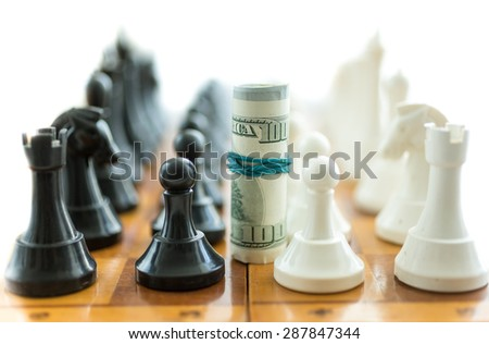 Conceptual shot of twisted dollar bills between white and black chess pieces