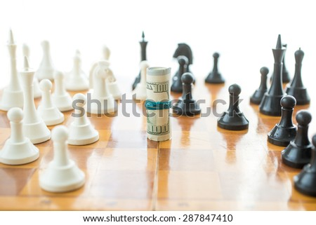 Conceptual shot of twisted money on wooden chessboard - stock photo