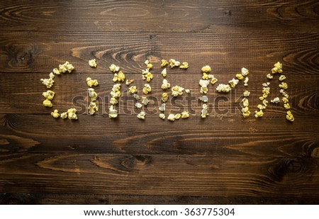 Conceptual shot of word Cinema written by popcorn and kernels on wooden background - stock photo