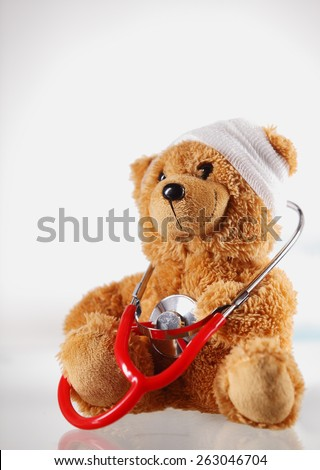 Conceptual Sick Brown Teddy Bear with Bandage on the Head and Checking Himself with Stethoscope Device. Isolated on White Background. - stock photo