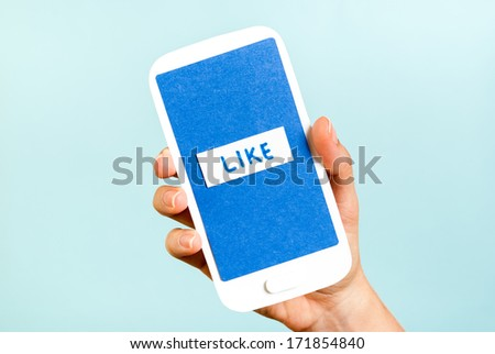 Conceptual smartphone showing like button on blue background - stock photo