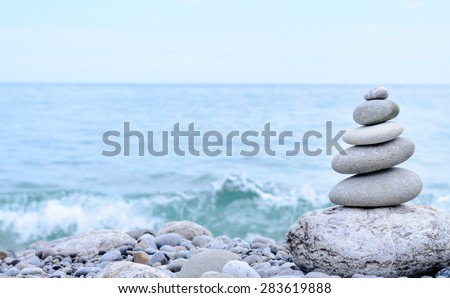 Conceptual Stack of Six Dry Stones at the Sea, from Biggest to Smallest Size - stock photo