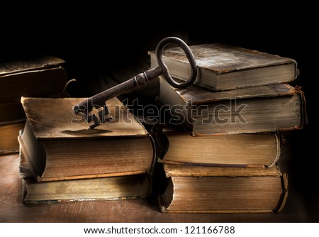 Conceptual still life image of old antique books and a big old key. - stock photo