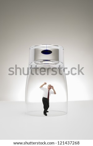 Conceptual studio image of a diminutive grey-haired senior business man trapped under a stylish modern glass or beaker hammering his fists against the glass yelling for attention to gain his freedom - stock photo