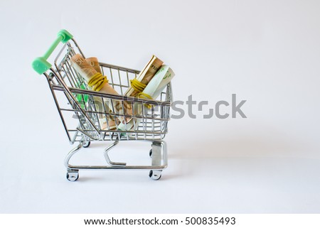 Conceptual studio shot of a bunch of euro banknotes filling a shopping cart on white background.
