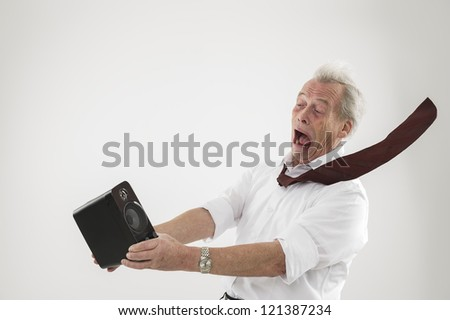 Conceptual studio shot over white of an old man being blasted by a sound wave from an audio speaker - stock photo