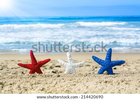 Conceptual summer holiday image of three red, white and blue starfish on the beach overlooking a turquoise ocean while celebrating the July fourth holiday.  - stock photo