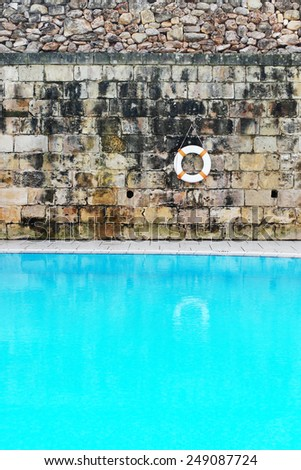 Conceptual Tranquil Old Swimming Pool with Clear Water, Emphasizing Lifebuoy Hanging on the Wall - stock photo