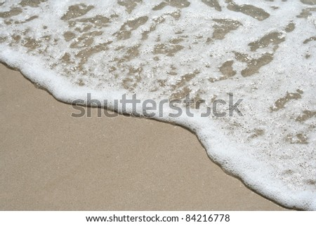 Conceptual wave of the sea on the sandy beach background - stock photo