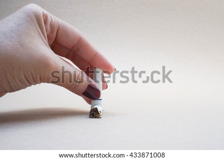 Conceptual wording of stop smoking by using left hand crush a cigarette  - stock photo